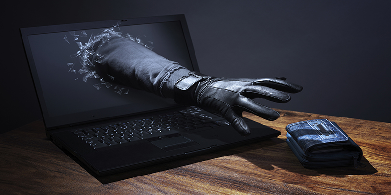 Stealing a purse through a laptop concept for computer hacker, network security and electronic banking security